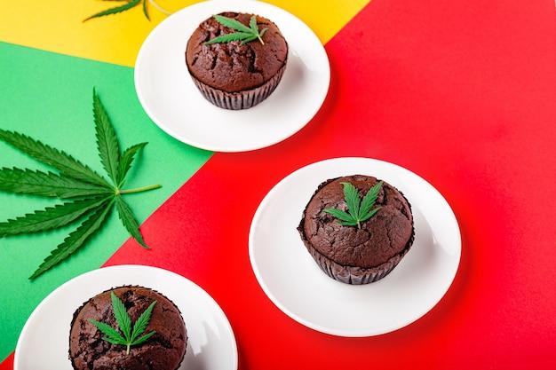 Muffin cupcake al cioccolato alla marijuana con cbd all'erba. droghe di canapa di marijuana medica nel dessert alimentare. muffin di erba con foglie di cannabis e cannabis serviti su sfondo rosso bandiera rastaman copia spazio.