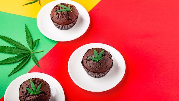 Muffin cupcake al cioccolato alla marijuana con cbd all'erba. droghe di canapa di marijuana medica nel dessert alimentare. muffin erbaccia con foglie di cannabis e cannabis servito su sfondo rosso bandiera rastaman banner web lungo.