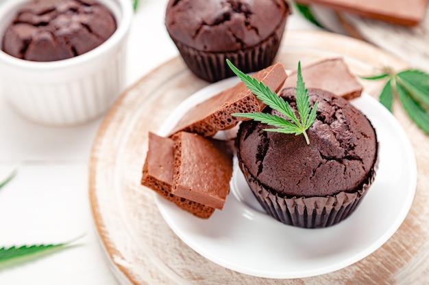 Muffin cupcake al cioccolato alla marijuana con cbd all'erba. droghe di canapa di marijuana medica nel dessert alimentare. muffin all'erba con cannabis, cioccolato al latte e foglie di cannabis serviti su un tavolo bianco piatto.