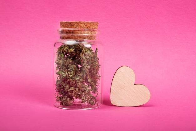 Barattolo di simbolo dell'amore della marijuana con boccioli di cannabis secchi e un cuore di legno su sfondo rosa Foto Premium