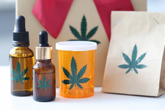 Pillole di marijuana e bottiglie con estratto in piedi sullo sfondo del regalo