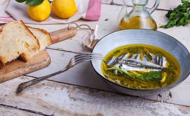 Acciughe marinate nel succo di limone con olio d'oliva aglio e prezzemolo. piatti estivi mediterranei tradizionali