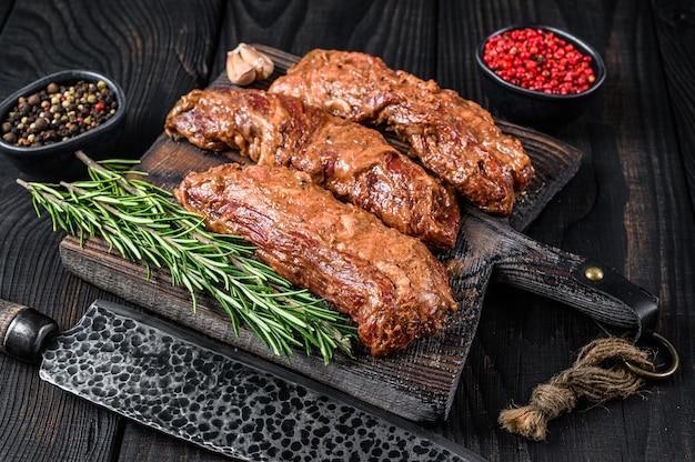 Bistecche di petto marinate in salsa barbecue su un tagliere di legno con erbe aromatiche