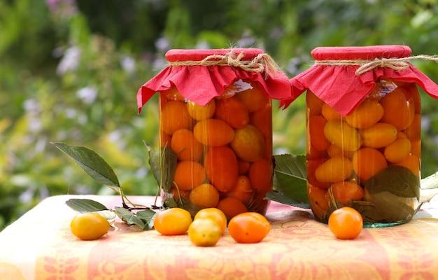 Pomodorini marinati in barattoli su un tavolo in giardino, primo piano