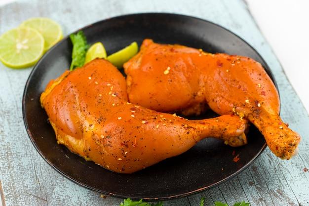 Coscia di pollo marinata senza pelle disposta in un piatto nero