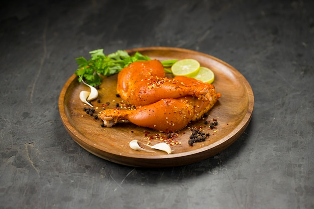 Coscia di pollo marinata senza pelle disposta su base di legno