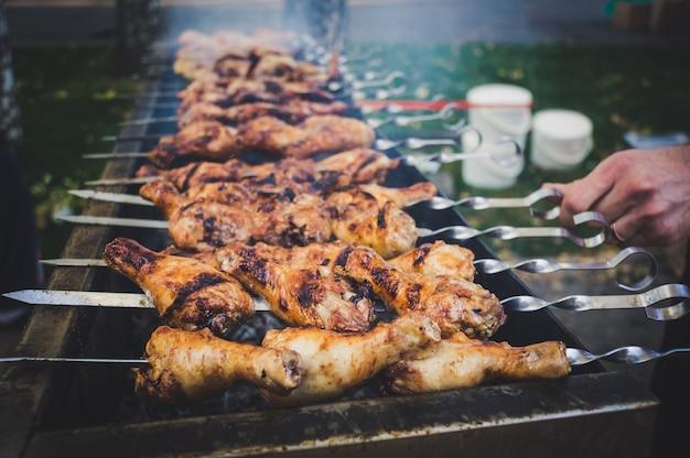 Cosce di pollo marinate fritte sulla griglia per barbecue fiammeggiante.