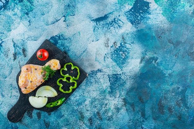 Coscia marinata e verdure a fette su un tagliere sulla superficie blu