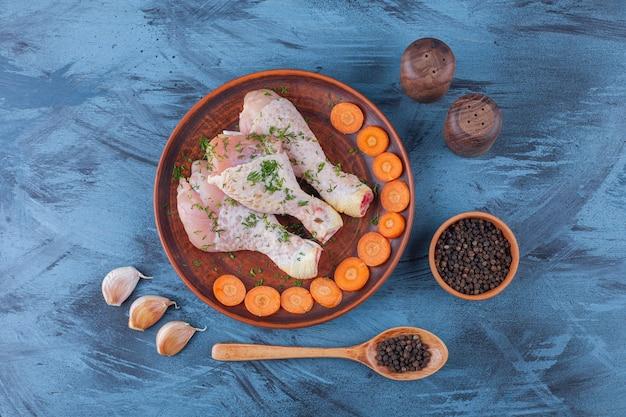 Cosce di pollo marinate e carote affettate su un piatto di legno accanto a spezie, cucchiaio e aglio, sul blu.