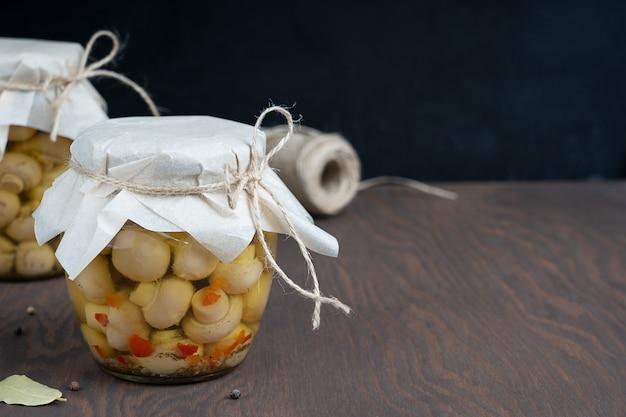 Funghi champignon marinati o fermentati in barattolo di vetro o vaso sul tavolo di legno scuro