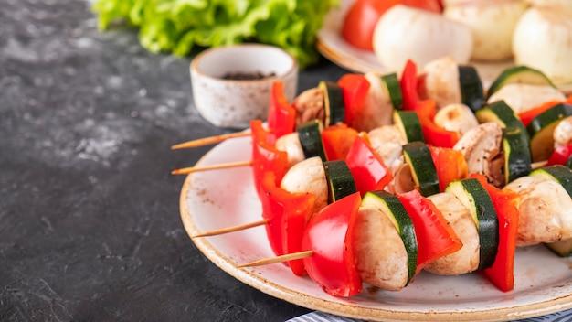 Verdure fresche marinate su spiedini di legno pronte da cuocere sul mangal. verdure alla griglia. spazio del testo