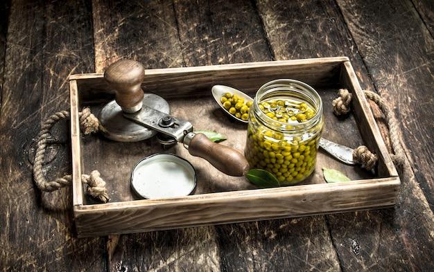 Piselli marinati con aggraffatrice su un vecchio vassoio. su uno sfondo di legno.