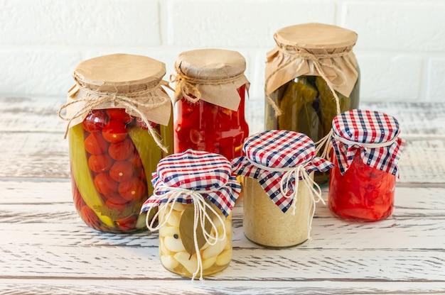 Vasi per conserve di varietà di sottaceti marinati. pomodori fatti in casa, cetrioli, aglio, zenzero e sottaceti al rafano. cibo fermentato.