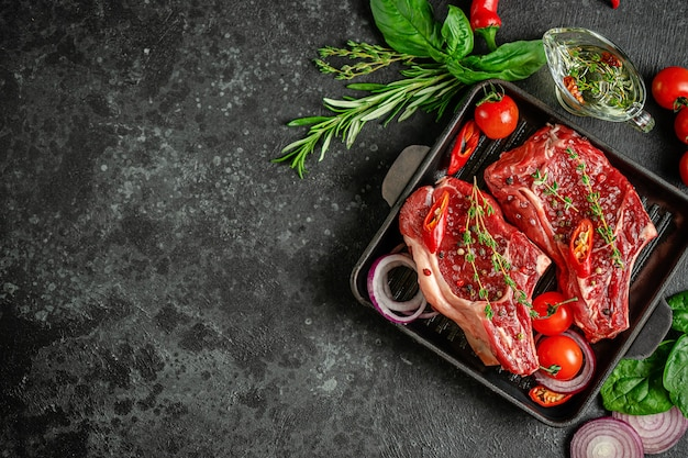 Bistecche di osso di vitello crude marinate sulla bistecchiera con ingredienti da cucina su sfondo scuro