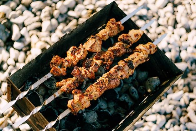 Shashlik marinato che si prepara su una griglia per barbecue su shashlik al carbone o shish kebab popolare in Foto Premium