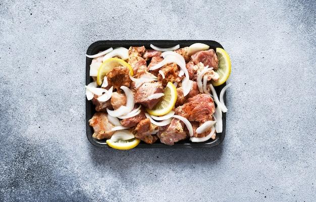 Shish kebab marinato con cipolla e limone. carne di maiale con spezie su un vassoio.