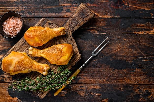 Cosce di pollo marinate e affumicate su un tagliere di legno