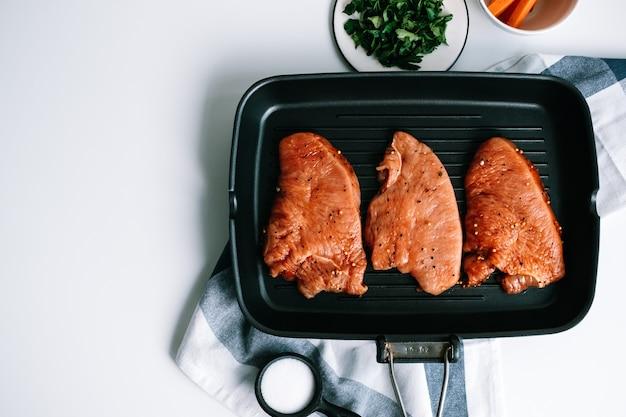 Bistecca di tacchino marinata con spezie in una bistecchiera nera sul tavolo.