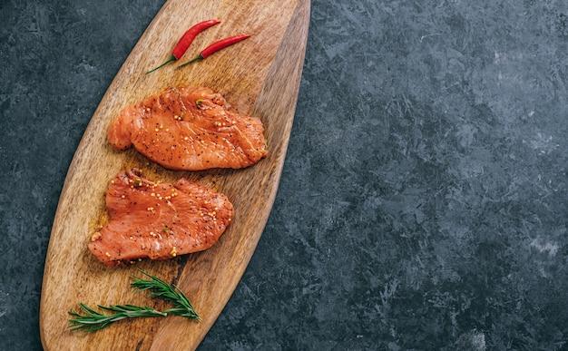 Bistecca di tacchino marinata su una tavola di legno con rosmarino e peperoncino, copia dello spazio.