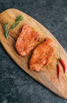 Bistecca di tacchino marinata su una tavola di legno con rosmarino e peperoncino.