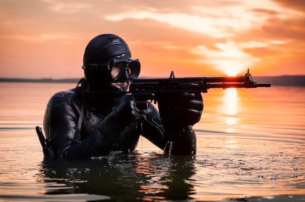 Il marine esce dall'acqua e si avvicina al bersaglio con le armi in mano. il concetto di videogiochi, pubblicità, instabilità nel mondo, conflitti tra paesi. tecnica mista