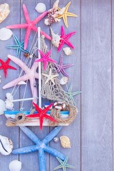 Vita marina con conchiglie, stelle marine e barca su assi di legno