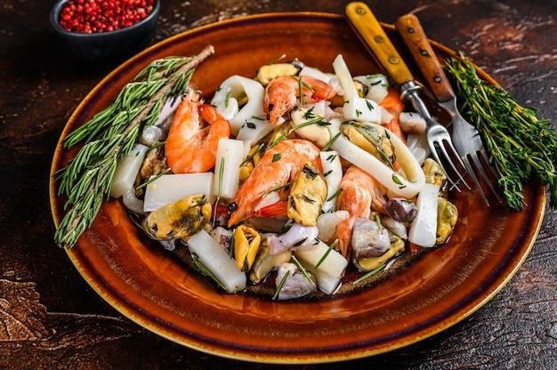 Cocktail di frutti di mare marini con gamberi, gamberi, cozze, calamari e polpi su un tagliere. fondo in legno scuro. vista dall'alto.