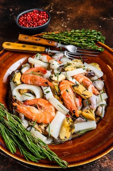 Cocktail di mare di mare con gamberi, scampi, cozze, calamari e polpo su tagliere.