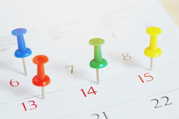 Contrassegna il giorno dell'evento con uno spillo. puntina da disegno nel concetto di calendario per timeline impegnata organizzare la pianificazione