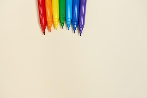 Marcatori arcobaleno di colori su carta gialla per il disegno. lay piatto. vista dall'alto dei pennarelli.
