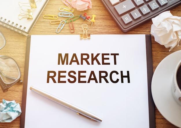 Concetto di ricerca di mercato. testo su notebook con strumenti per ufficio e tazza di caffè