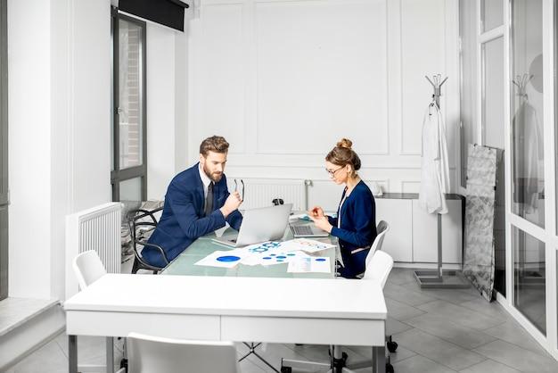 Team di manager di marketing o analityc vestito con abiti che lavorano con grafici cartacei e laptop all'interno dell'ufficio bianco