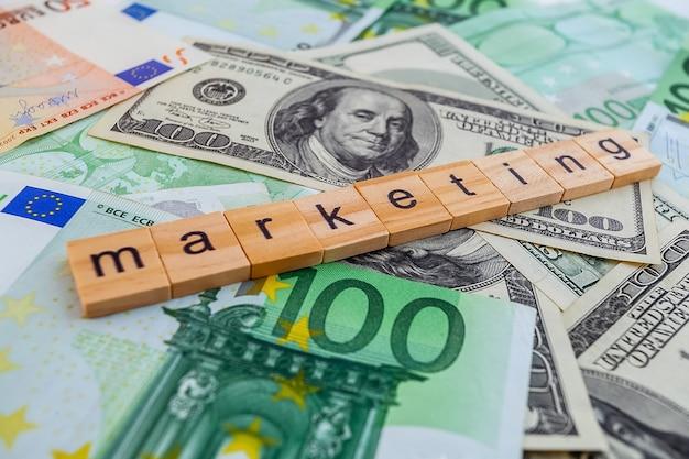 Iscrizione di marketing su cubi di legno sulla trama di dollari americani e banconote in euro
