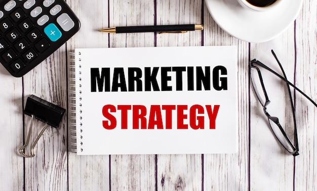 Strategia di marketing è scritta in un blocco note bianco vicino a una calcolatrice, caffè, occhiali e una penna. concetto di affari