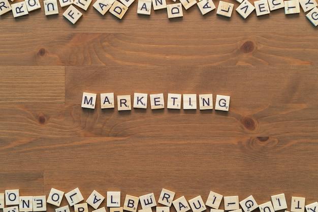 Il testo di marketing ha scritto con lettere scrabble isolate sulla scrivania in legno. modello di sfondo.