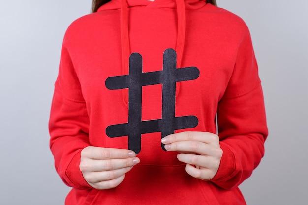 Concetto di vendita digitale di tweet del sito web della gioventù di marketing. ritagliata primo piano foto di allegro positivo felice ottimista sorriso a trentadue denti che tiene grande grande hashtag nero in palmo isolato sfondo grigio