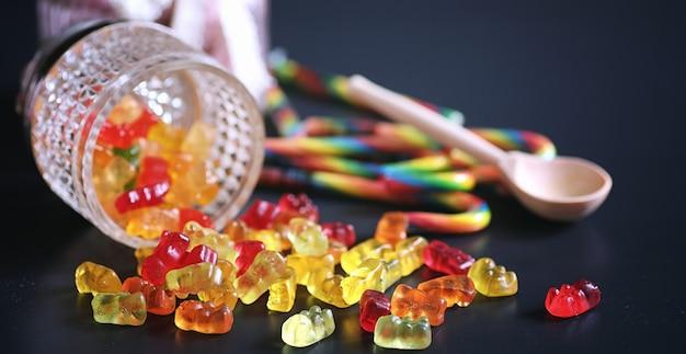 Marmellata in un vaso sul tavolo. dolci in una ciotola su sfondo nero. caramelle di gelatina multicolori per bambini.