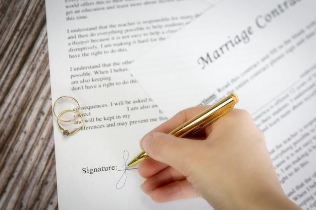 Contratto di matrimonio con due fedi nuziali dorate e penna d'oro, accordo prematrimoniale, macro close up, segno con firma, documento, concetto di accordo romanticismo
