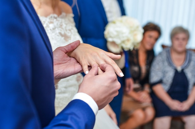 Mani del matrimonio con anelli. birde indossa l'anello al dito dello sposo