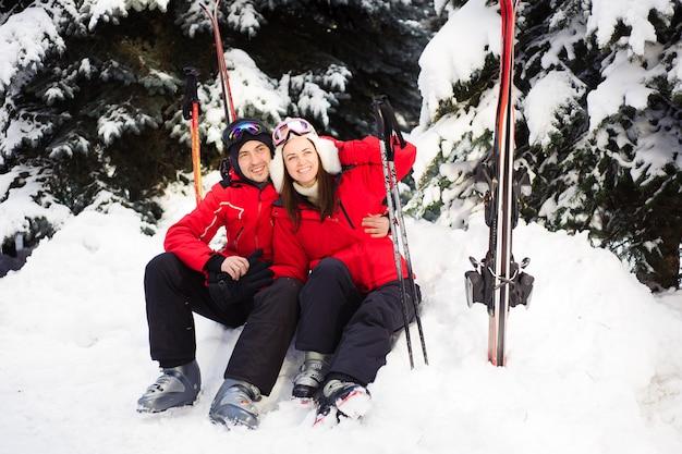 Coppia sposata in giacche luminose che preparano sciare insieme nella foresta di inverno.