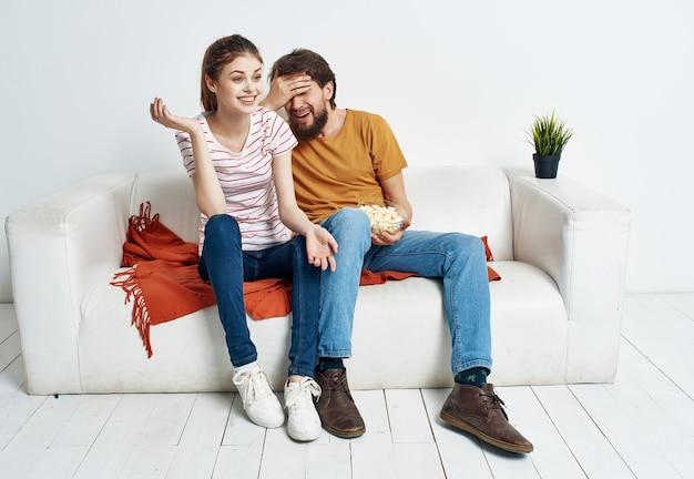 La coppia sposata a casa sul divano riposa il divertimento dei popcorn