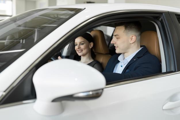 Coppia sposata marito e moglie seduti in macchina in una concessionaria di automobili