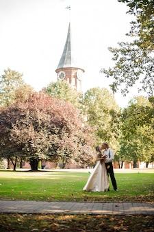 Coppia sposata baciare su un campo di erba verde con alberi e vecchia cattedrale in background il giorno d'estate