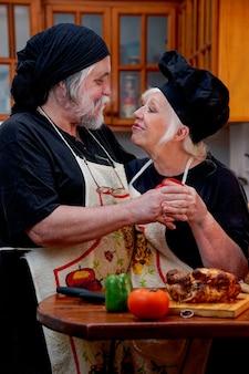 Coppia sposata uomo e donna che cucinano felicemente nella cucina di casa