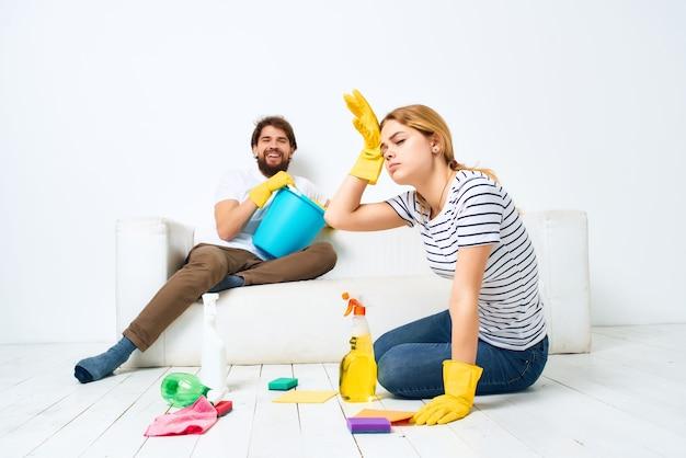Coppia sposata vicino al divano che pulisce lo sfondo chiaro dell'appartamento