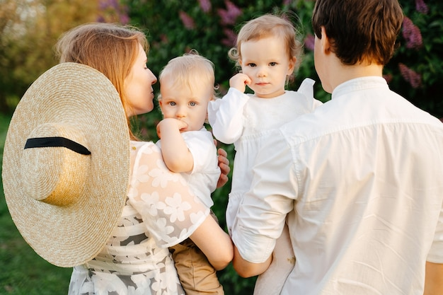 I genitori di una coppia sposata tengono i gemelli fratello e sorella di verde nei bambini del parco