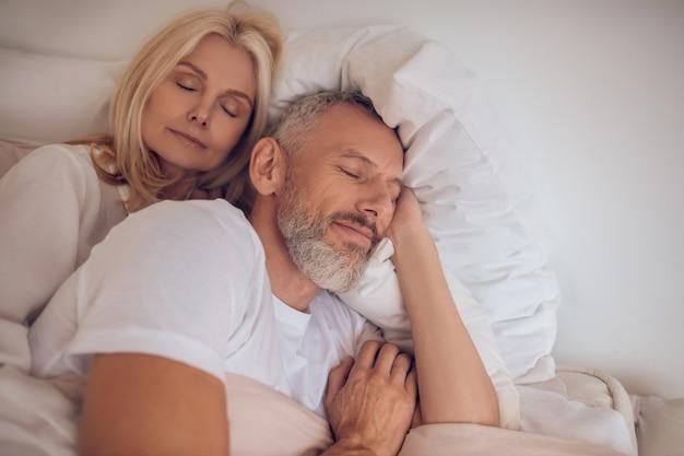 Coppia sposata che dorme su un letto e sembra tranquilla