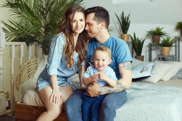 Coppia sposata e il loro piccolo bambino in braccio. giovane famiglia a casa la mattina del giorno libero