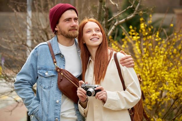 Coppia di sposi viaggiatori in abbigliamento casual camminano nella foresta primaverile, con fotocamera retrò, scattando foto di luoghi intorno, in contemplazione. ritratto di uomo caucasico e donna che si godono il viaggio insieme