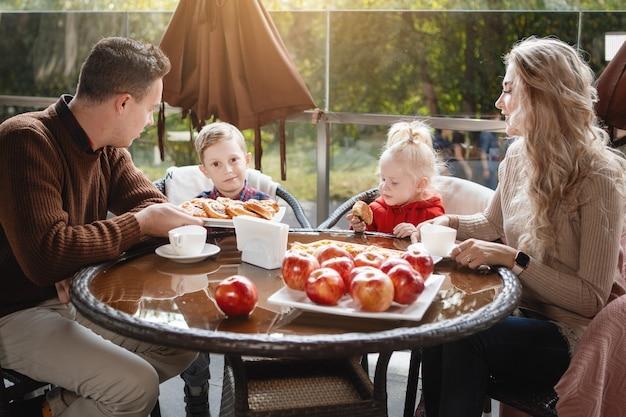 Coppia sposata con figli, figlia e figlio a un tavolo in un caffè. felice coppia tradizionale, felicità familiare.